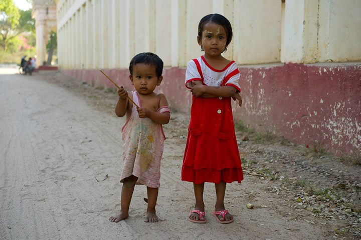 Siblings play in the street, Myanmar