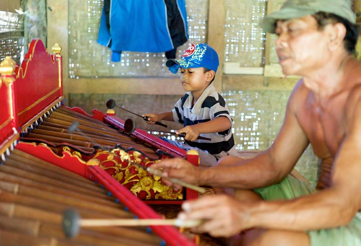 Little boy learning from his father how to play the Rindik