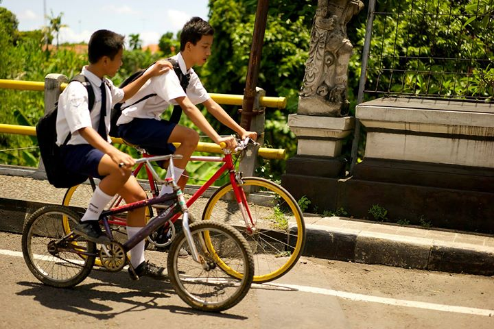 Students riding home on the road from Medewi to Negara, Bali, Indonesia