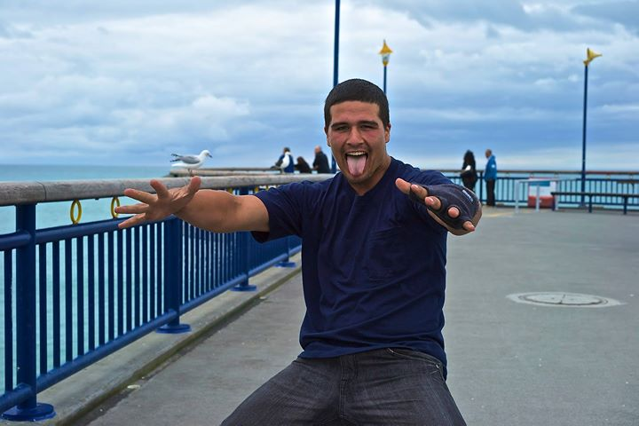 Tipene, a young Maori imitating one of the All Blacks postures, New Brighton's Pier, NZ