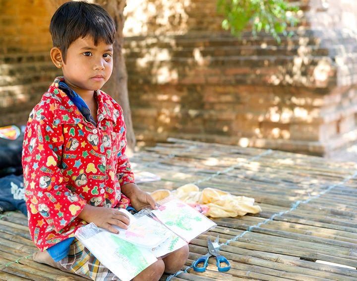 Girl drawing under a tree near Old Bagan, Bagan Region, Myanmar