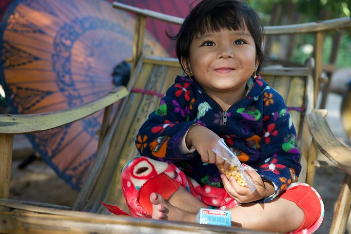 Little girl eating corn beans in Nyaung-U, Bago Region, Myanmar