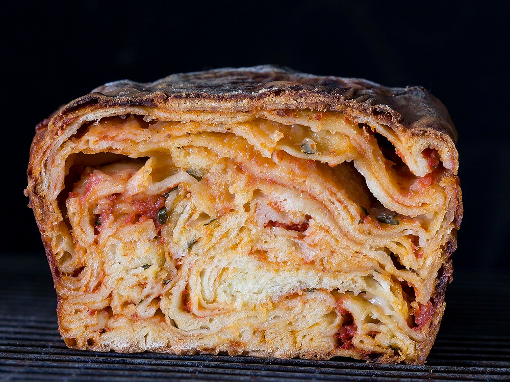 Scaccia A street food popular in its native Ragusa, scaccia is an exercise in rustic simplicity: A pizza-style dough is rolled super-thin, smeared with tomato sauce, showered with D.O.P. caciocavallo cheese, and folded into a lasagna-like loaf.