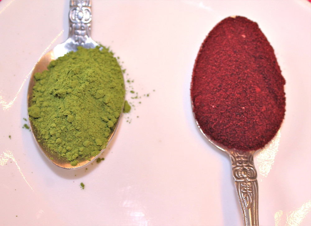 Two teaspoons on a white plate - one spoon is full of green powder, the other is full of red powder