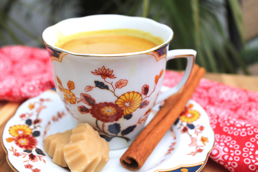 Chai tea in a teacup on a plate with maple pieces and a cinnamon stick