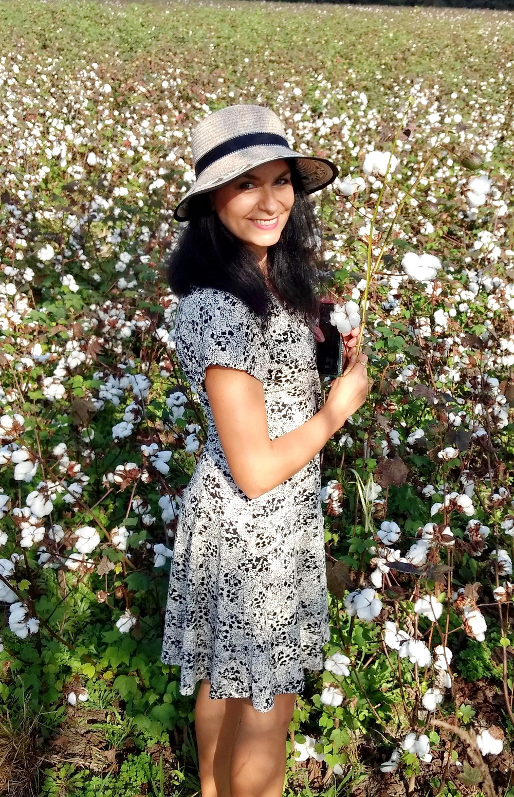 Woman in a hat and sundress standing in front of a cotton field