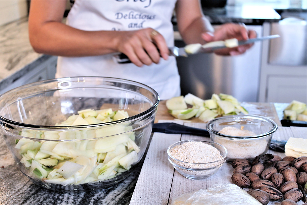 Glass bowl full of chopped apples next to a small bowl of oat flour in the foreground with a woman chopping apples in the background