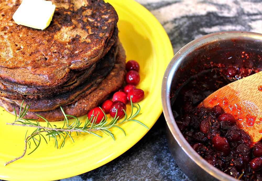 Stack of homemade buckwheat pancakes on a yellow plate with homemade cranberry sauce in a saucepan
