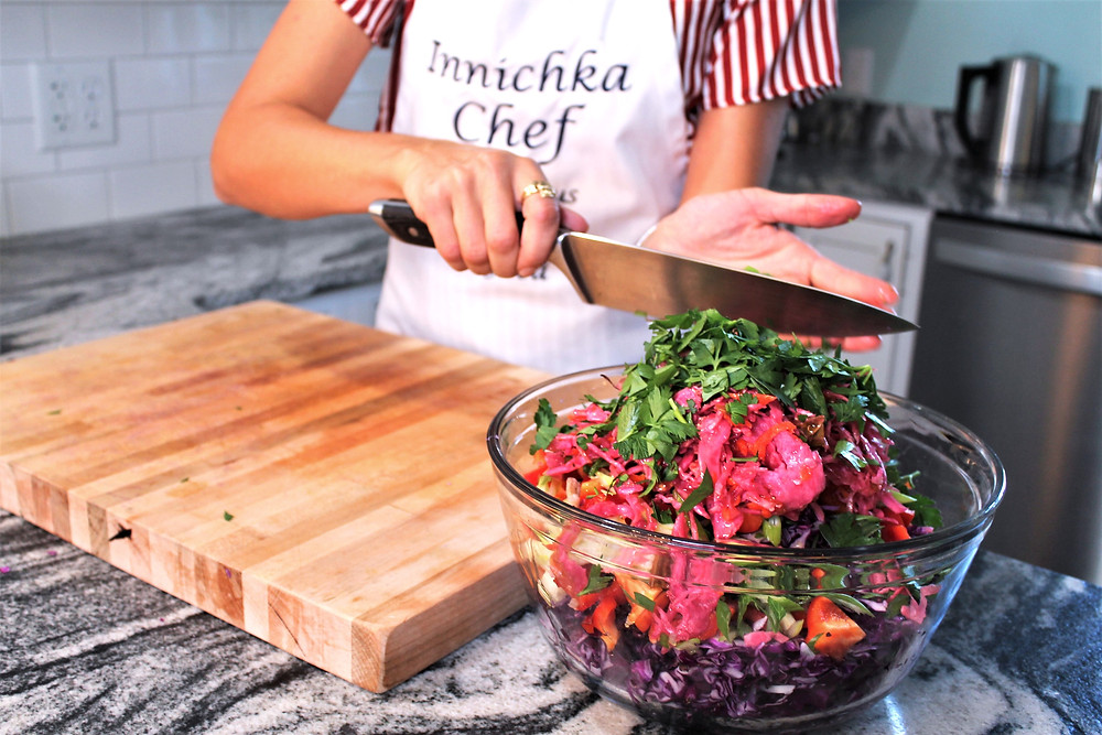 Scooping fresh chopped herbs onto a colorful vegetable salad topped with red sauerkraut
