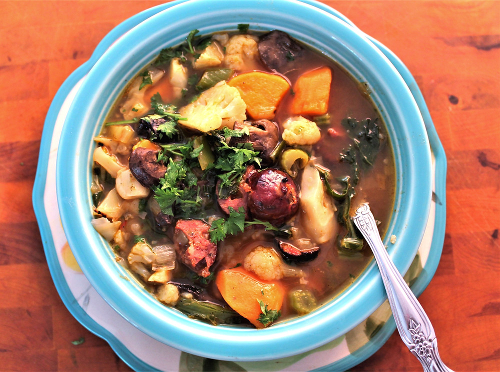 Winter soup with sweet potato, cauliflower, kale, mushrooms, and sausage in a blue bowl