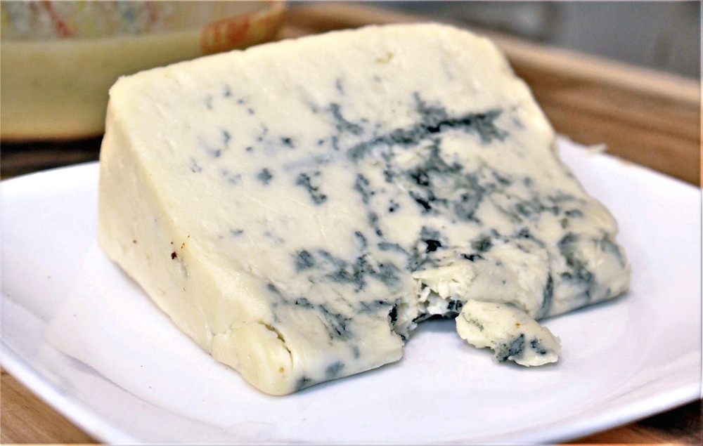 Wedge of blue cheese on a white plate