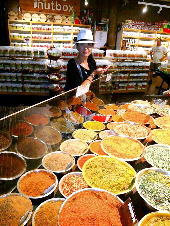 Woman in a white hat standing in front of bins full of a variety of spices