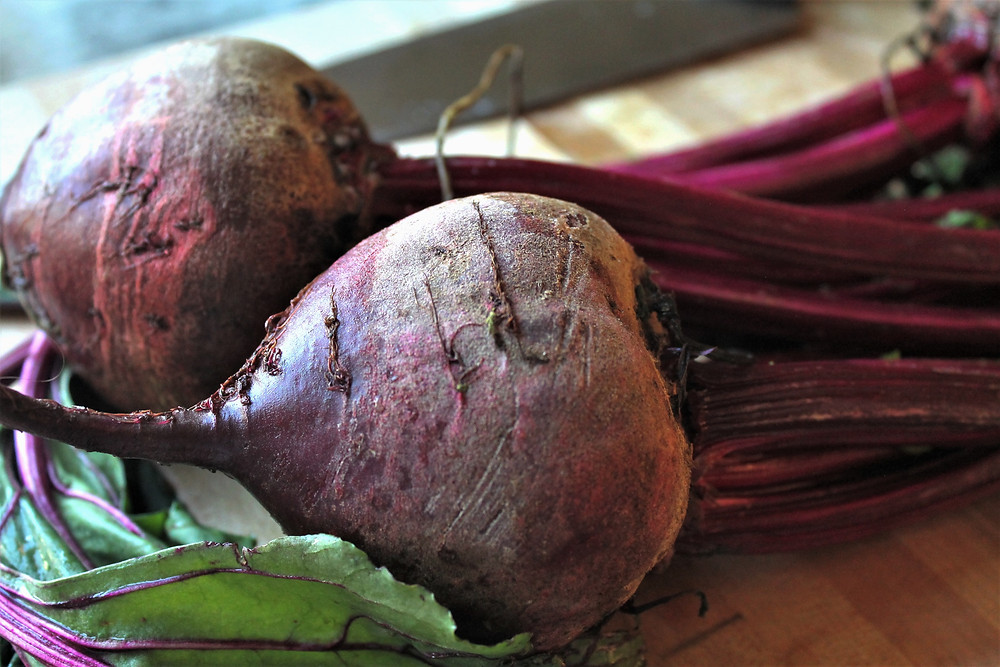 Unpeeled beets on a cutting board