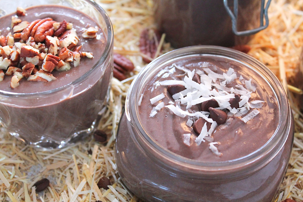 Chocolate pastry cream in jars topped with nuts, chocolate chips, and coconut sitting on a pile of straw