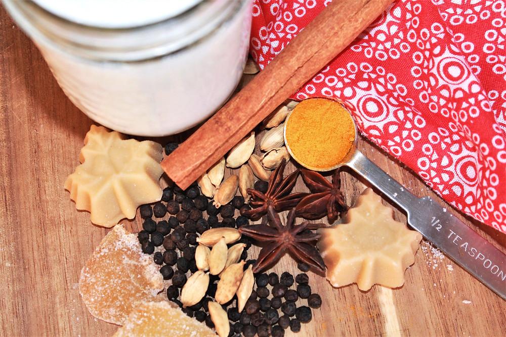 Ingredients to make chai tea: milk, cinnamon stick, turmeric, cardamom pods, maple, ginger, black peppercorns