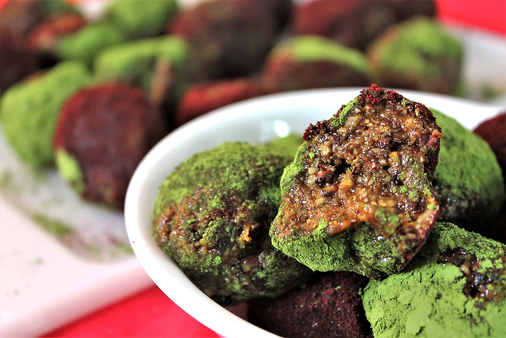 Nut and date balls coated in red and green powder in a white bowl