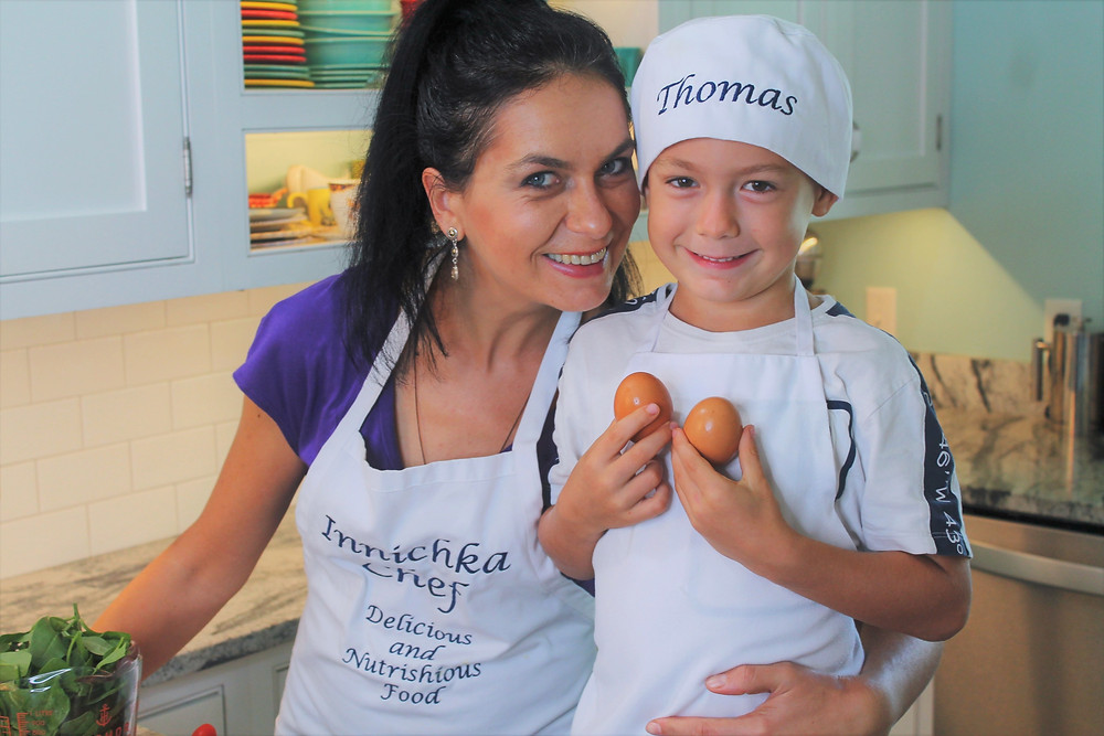 Woman and young boy smiling in the kitchen while the boy holds two eggs