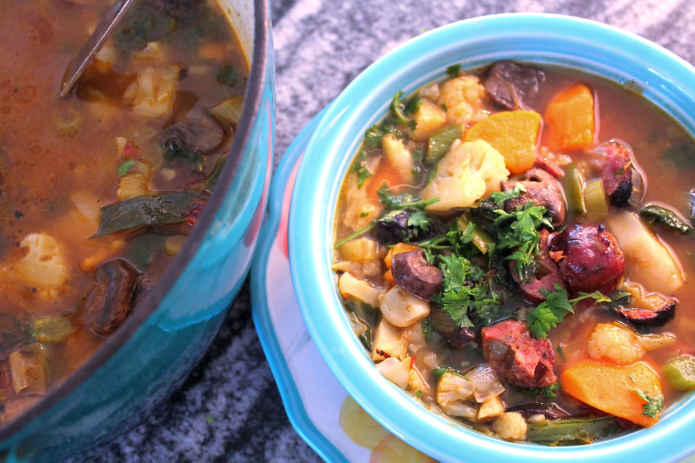 Winter soup with sweet potatoes, cauliflower, and sausage in a blue bowl