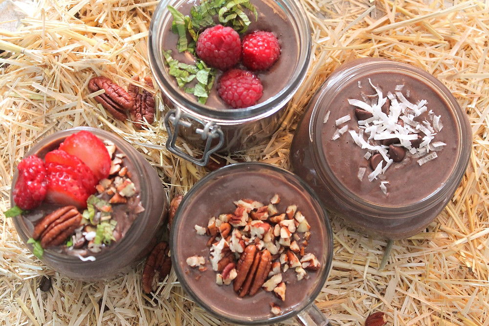 Four jars of chocolate pastry cream on a straw background; they're topped with fruit, nuts, coconut, and chocolate chips
