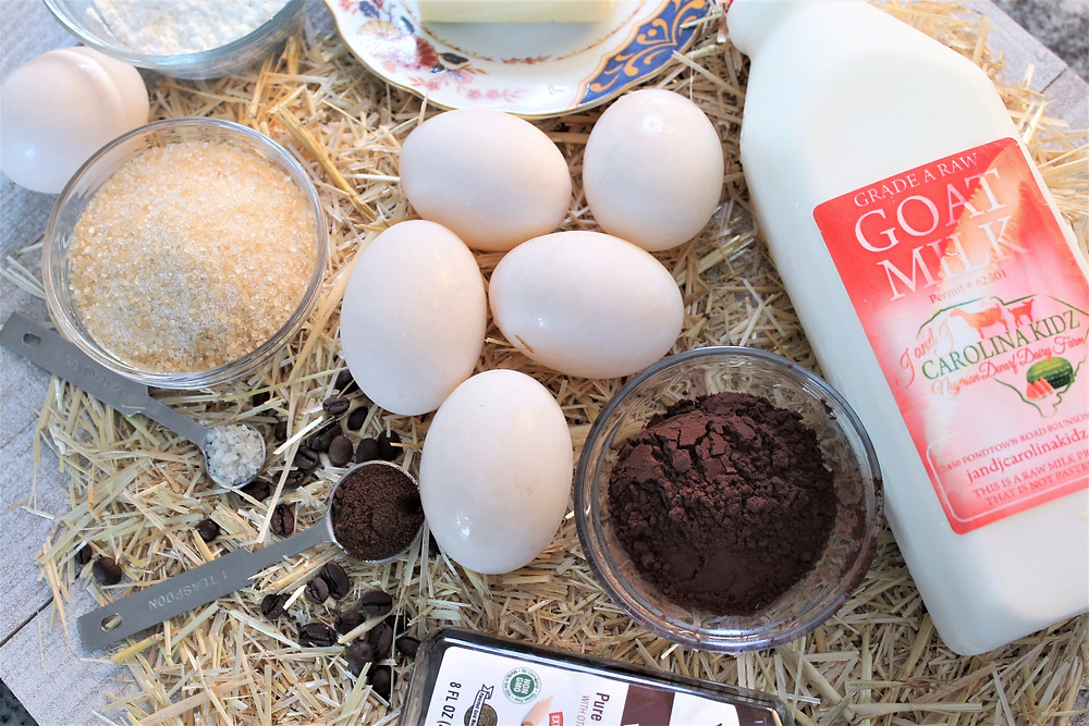 Ingredients on a bed of straw: sugar, duck eggs, butter, corn starch, goat milk, cocoa powder, vanilla, espresso powder, and chocolate chips