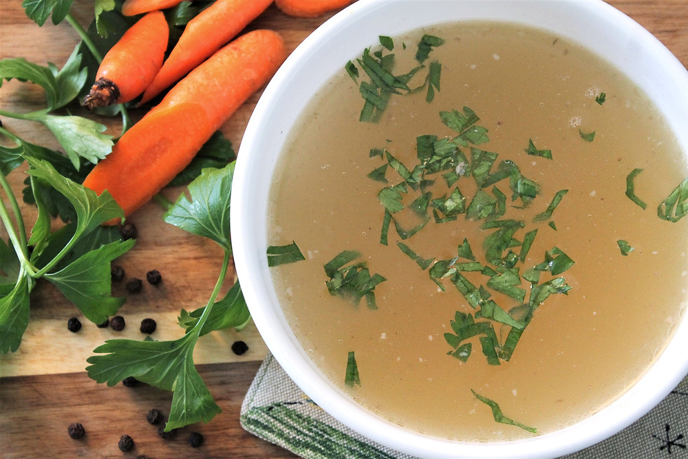 Bowl of chicken stock with herbs floating in it, next to a few carrots