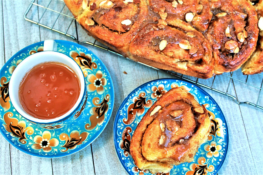Homemade almond butter cinnamon rolls with a cup of tea