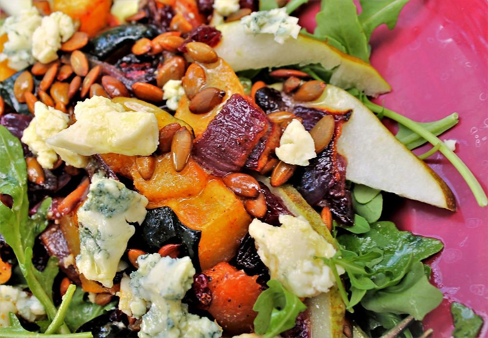 Plate of homemade maple roasted squash salad with black truffle vinaigrette