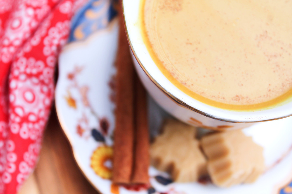 Close up of chai tea in a teacup on a plate with maple pieces and a cinnamon stick