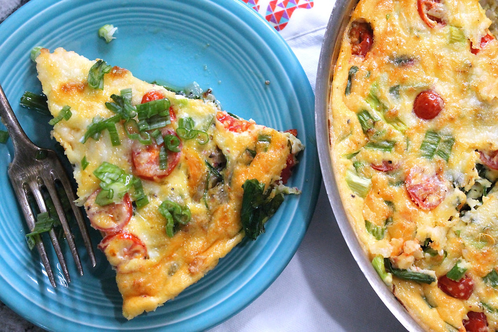Slice of frittata with sweet potatoes, tomatoes, and cheese; topped with green onions