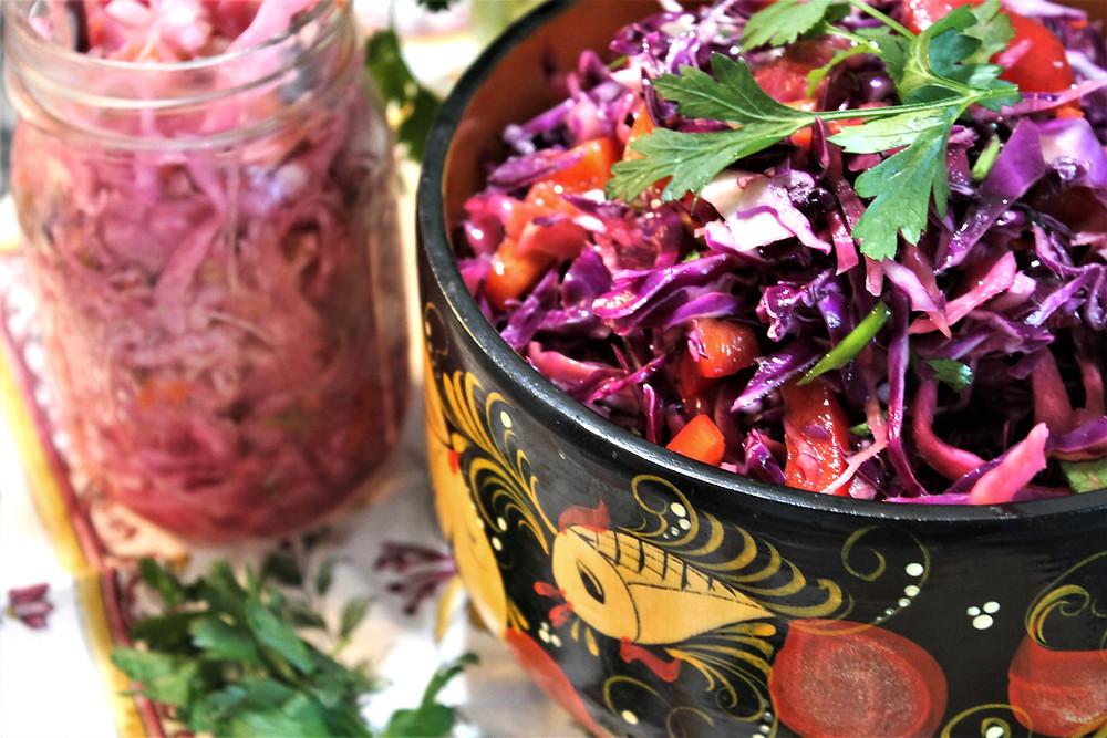 Colorful purple sauerkraut salad in a bowl next to a jar of sauerkraut