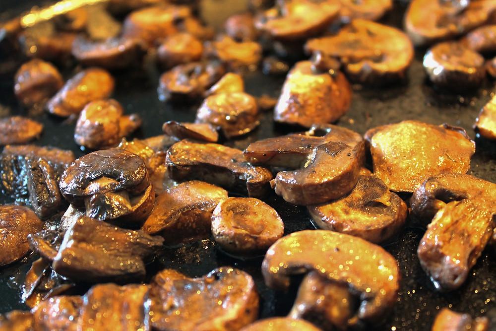 Mushrooms sautéing in a pan