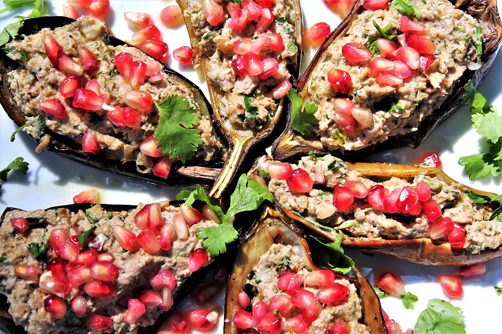 Plate full of eggplant boats with walnut meat and pomegranate seeds