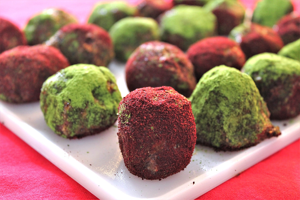 Nut and date balls coated in red and green powder sitting on a white plate on a red tablecloth