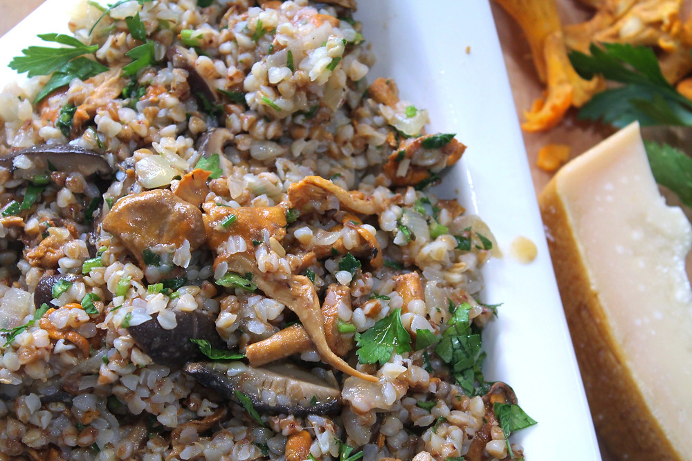 Buckwheat risotto with shitake mushrooms and chanterelles in a triangular white bowl with a wedge of cheese beside it