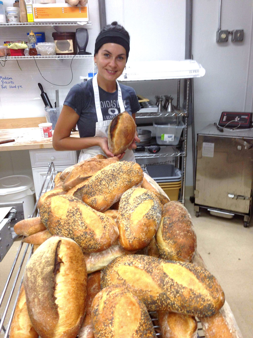 Woman holding a small loaf of bread behind a large pile of bread