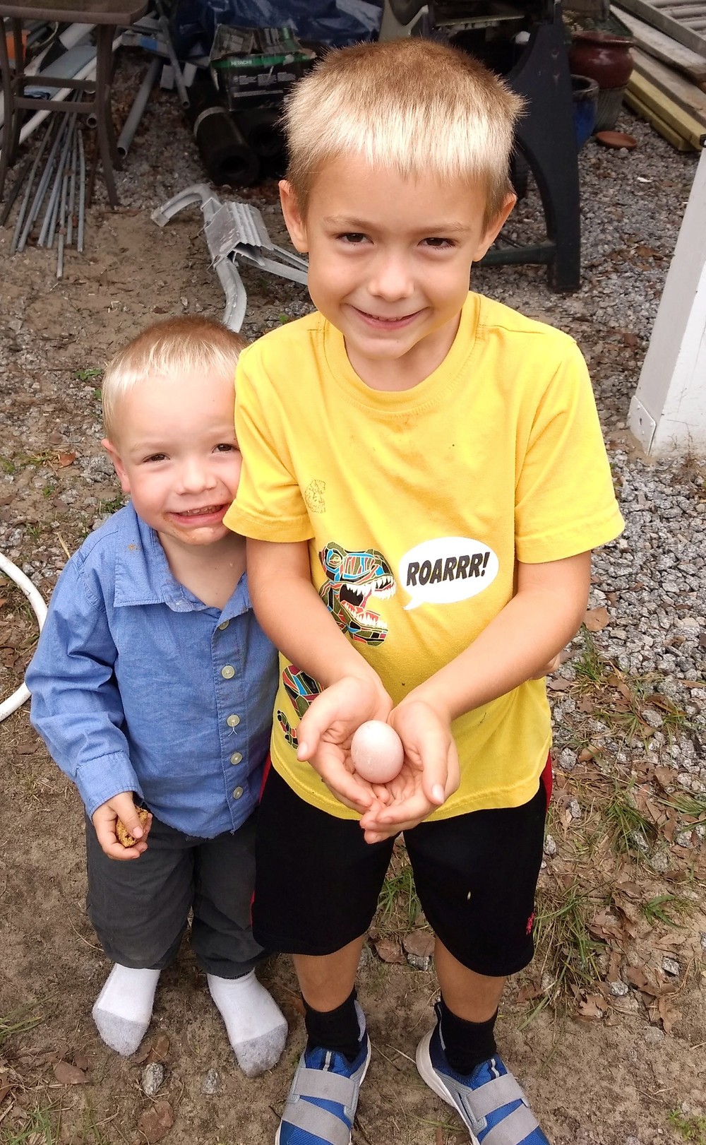 Two young boys standing next to each other; one of them is holding a small egg