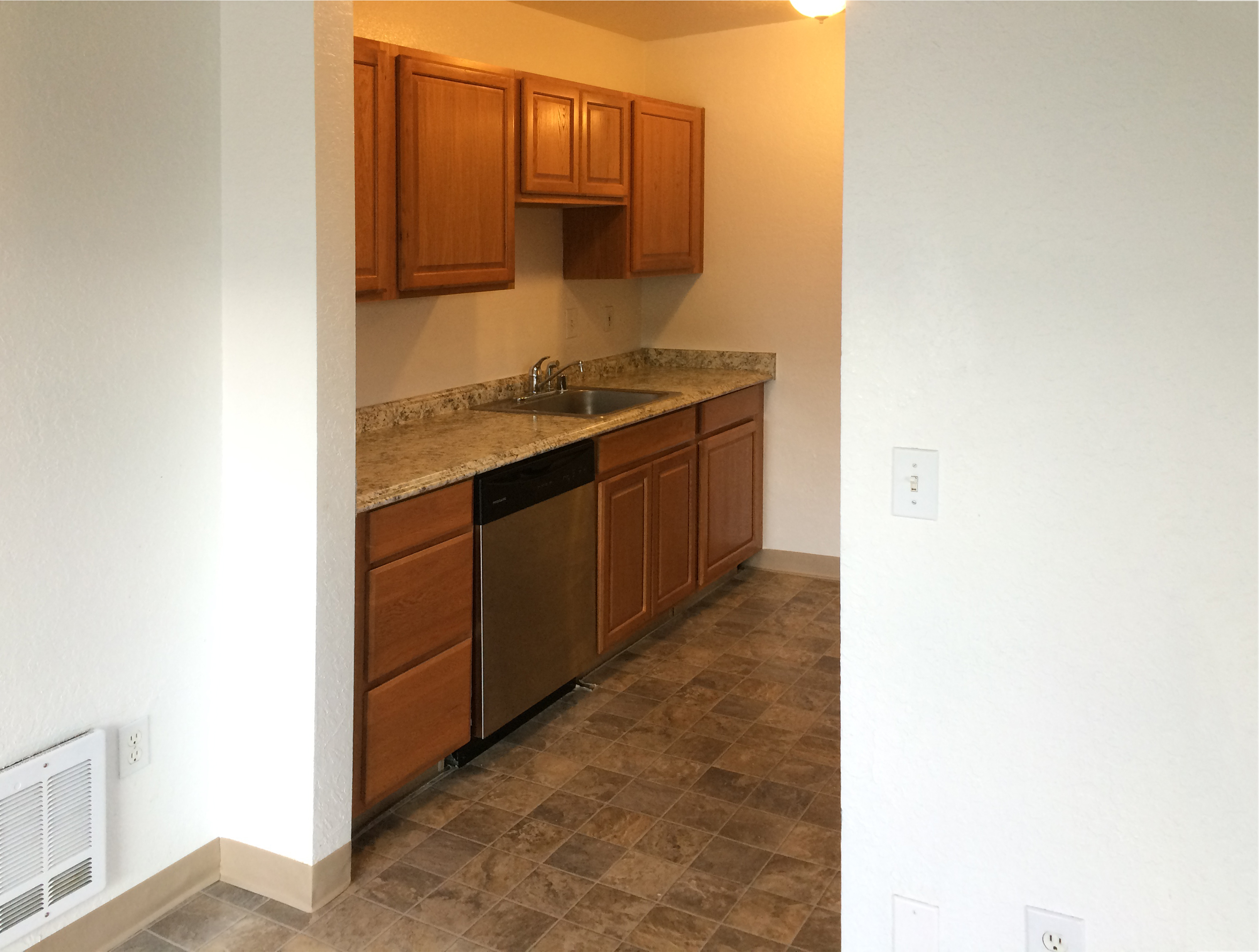 Kitchen complete with range, refrigerator, dishwasher, and garbage disposal in the sink.
