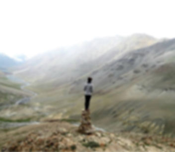 Woman on a cairn looking down a valley