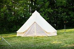 Es steht ein aufgestelltes 5 Meter Baumwollzelt da mit Blick zum Zelteingang. Es lädt ein dort zu übernachten und sich wohl zu fühlen. Die Grösse und die Form des Zeltes soll die Neugier am Produkt erwecken.