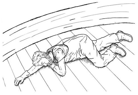 Unconcious person on the deck of a commercial fishing boat. Place the breathing, unconscious person in the recovery position to help maintain an open airway.