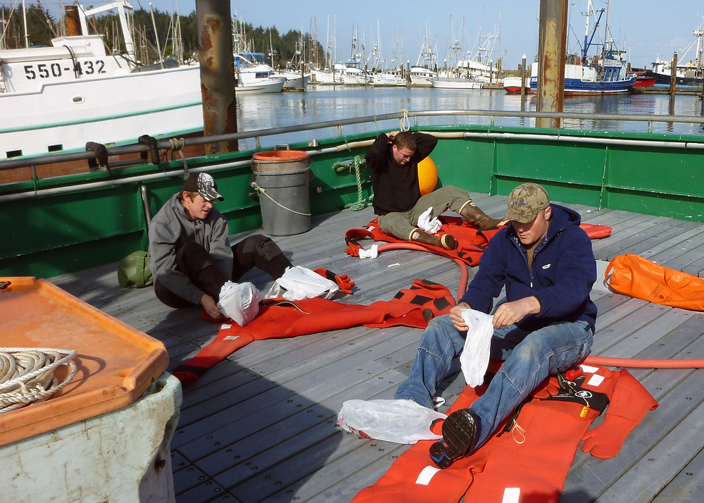 Commercial fishermen practicing the donning of immersion suits during an emergency procedures drill.