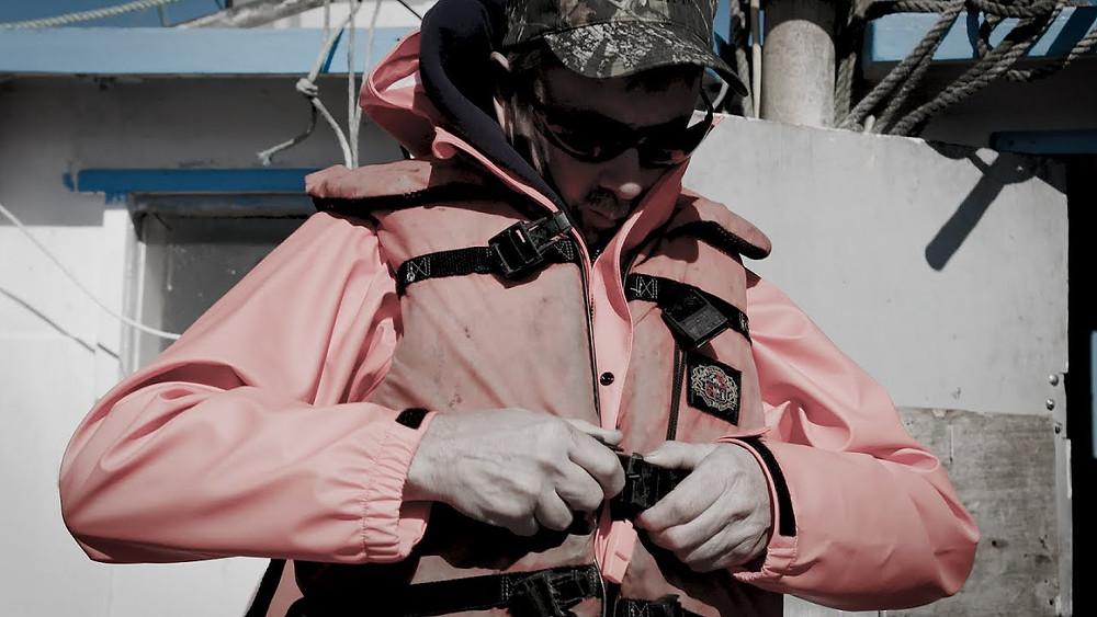 Commercial fisherman, Stan Jones, buckles his life vest before working on deck.