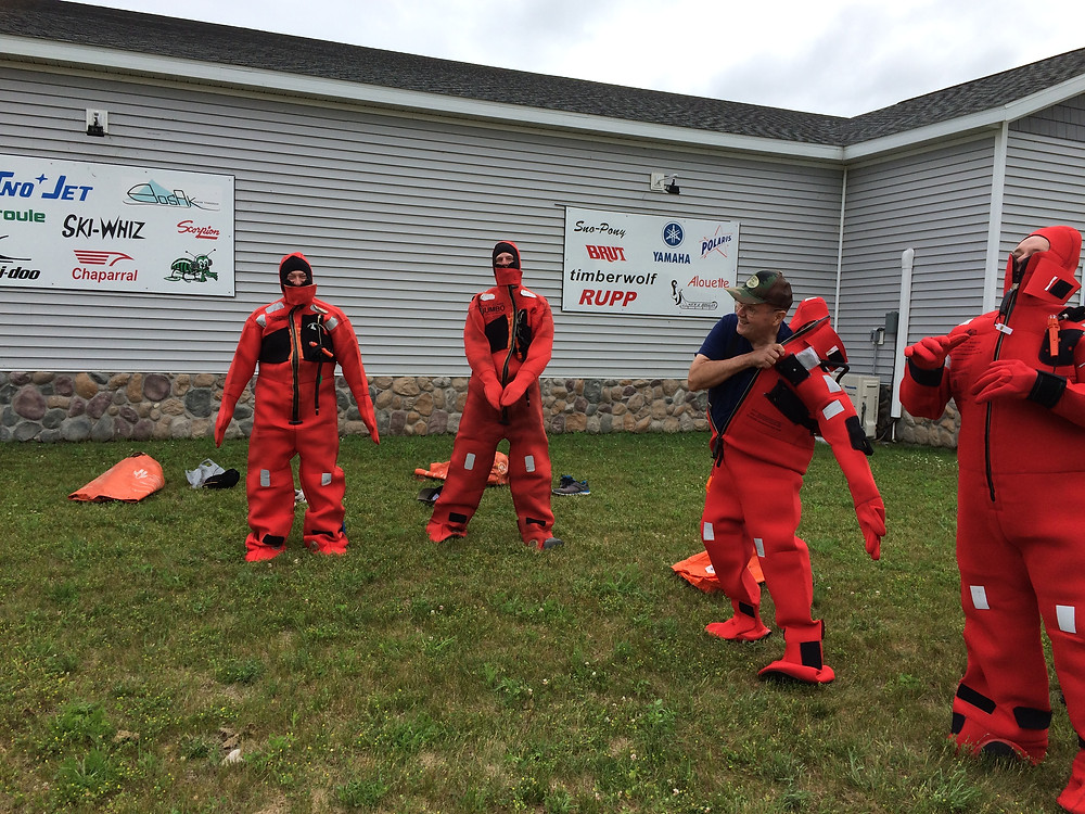 Chippewa/Ottawa commercial fishermen practicing with immersions suits in Naubinway, Upper Peninsula, MIchigan in AMSEA Drill Conductor workshop held in the Top of the World Snowmobile museum meeting room.