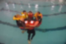 AMSEA students practicing cold-wter safety skills in swimming pool.