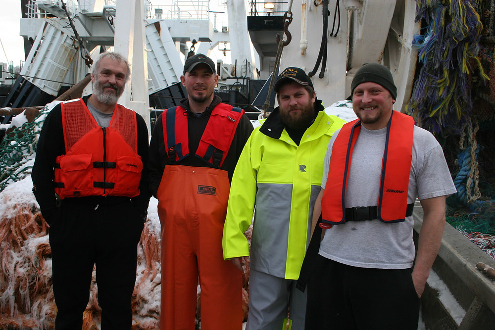 Commercial fishermen, crew on a fishing trawler wearing personal flotation devices (PFDs).