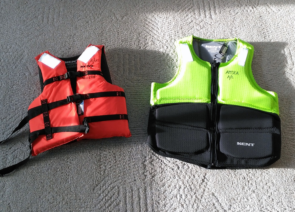 An approved Type-III on the left and a non-approved foam PFD on the right, both manufactured by Kent.