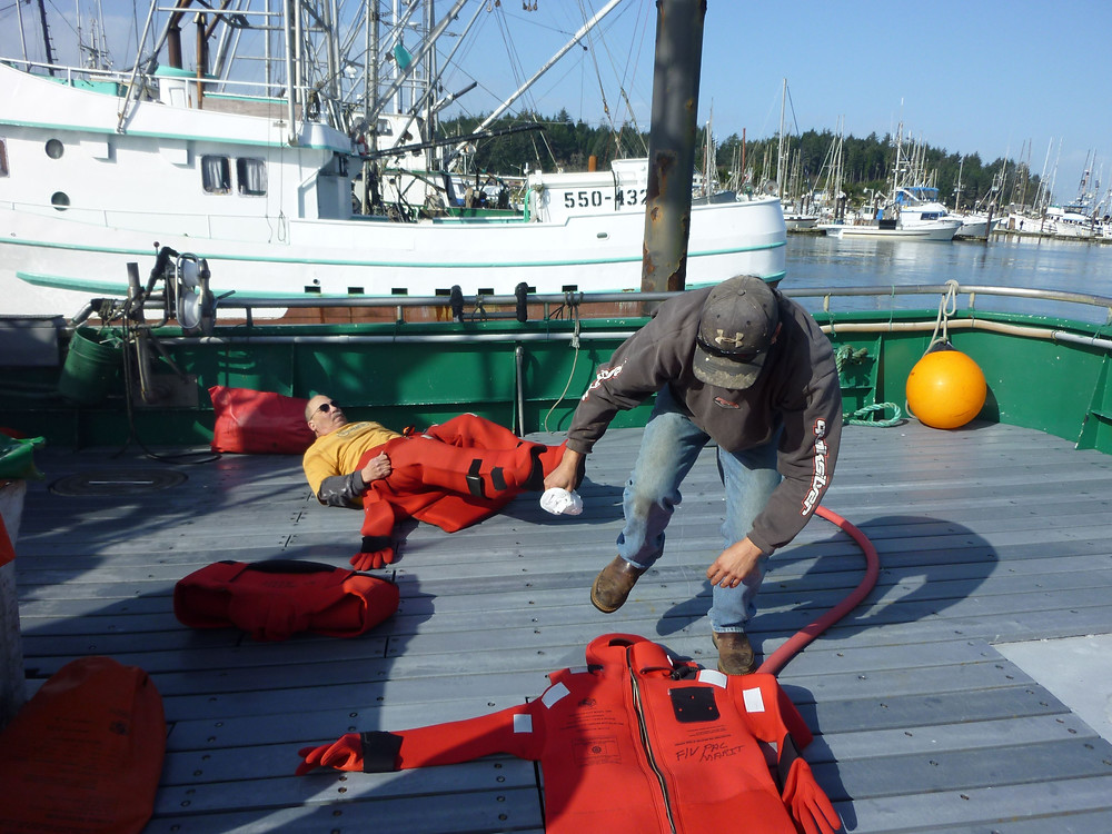 Commercial fishermen practice donning immersions suits during an onboard emergency procedures drill.