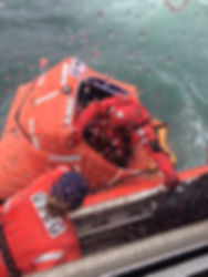 U.S. Coast Guard rescues mariners from an inflatable life raft.