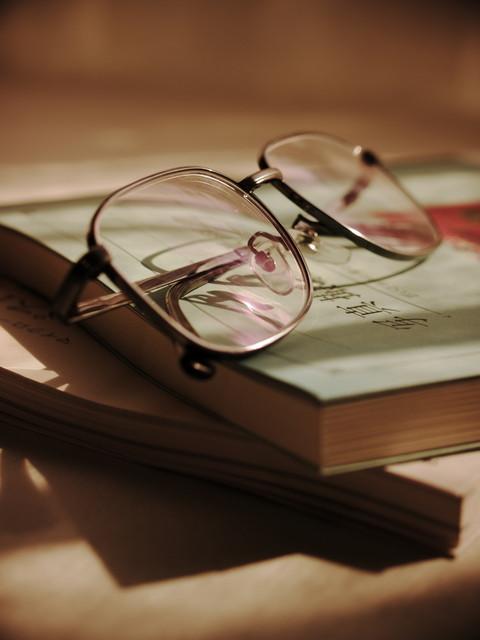 机に散らかっている眼鏡と本