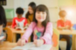 asian-girl-reading-book-smiling-camera-r